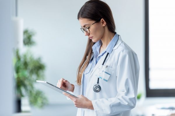 female-doctor-using-her-digital-tablet-while-stand-3AFJ8BH-2-600x400